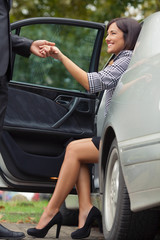 Attractive young woman getting out of the car with the help of a gentleman