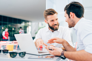 Two young modern businessman using laptop