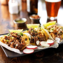three authentic mexican street tacos with barbacoa, carnitas and chicken