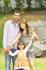 Adorable hispanic family of three posing in garden environment