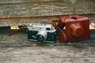 Vintage camera on wooden bench in autumn park