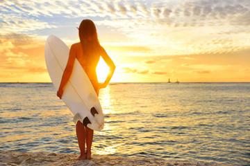 Surfing surfer girl looking at ocean beach sunset