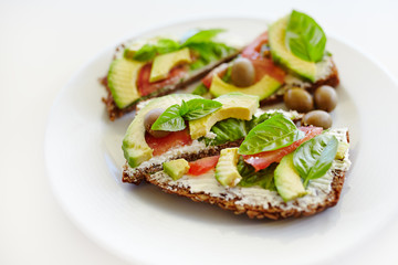 Healthy sandwich with whole-grain bread, avocado, tomato, basil leaves and olives on plate; healthy eating; organic food;