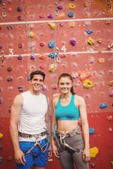 Couple climbing up rock wall