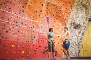 Fit couple at the rock climbing wall