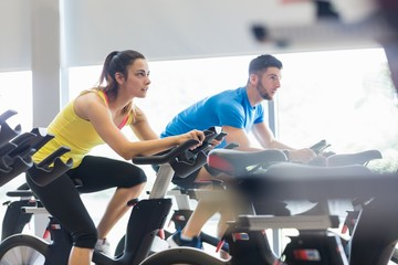 Couple using exercise bikes together