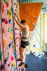 Fit couple rock climbing indoors