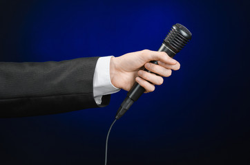 Business speech and topic: a man in a black suit holding a black microphone on a dark blue background in studio isolated