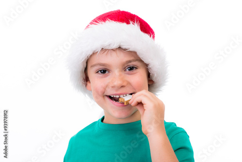 kleiner junge mit weihnachtsmann m tze isst ein pl tzchen. Black Bedroom Furniture Sets. Home Design Ideas