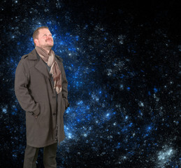 Middle-aged man in a coat looking up on starry universe