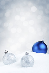 Blue and silver Christmas baubles on snow, silver background