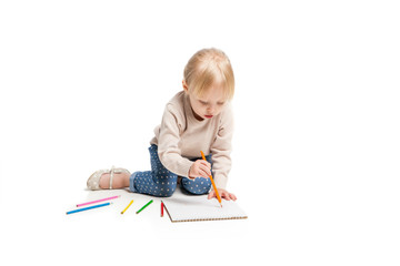 Little cute girl sitting on floor and drawing with colourful