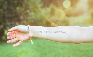 Female arm with text -I'm still waiting- written in skin
