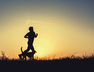 Sunset runner with dog silhouette