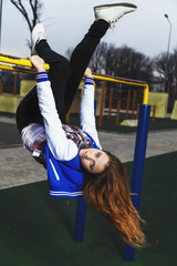 Young girl hanging upside down on the playground