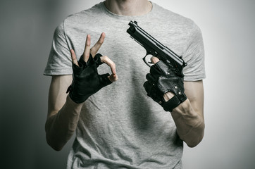 Horror and firearms topic: the killer with a gun in his hand in black gloves on a gray background in the studio