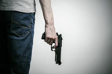 Horror and firearms topic: crazed killer with a gun on a gray background in the studio
