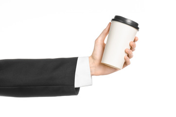 Business lunches coffee theme: businessman in a black suit holding a white blank paper cup of coffee with a brown plastic cap isolated on a white background in the studio, advertising coffee