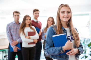 Smiling female student standing in classroom