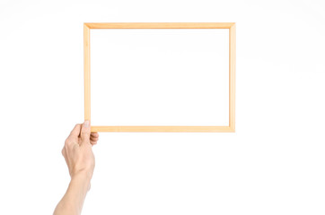 House decoration and Photo Frame topic: human hand holding a wooden picture frame isolated on a white background in the studio first-person view