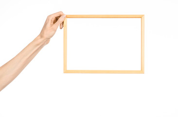 House decoration and Photo Frame topic: human hand holding a wooden picture frame isolated on a white background in studio