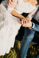 bride and groom clasped their hands