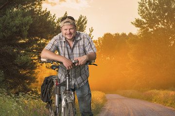 Tourist man standing with a bicycle with misty dawn at