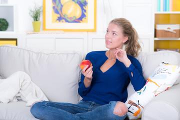blonde frau mit einem apfel auf der couch