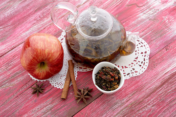 Ripe apple, cinnamon and fruit drink in glass teapot on wooden