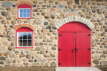 Bright Red Arched Door and Windows in a Stone Wall