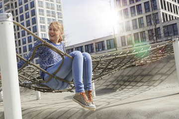 Young woman sitting on a climbing net in playground, Munich, Bavaria, Germany