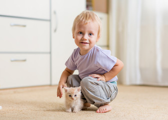 Toddler kid boy playing with a kitten in children room