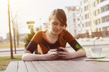 Young woman text messaging at sidewalk cafe, Munich, Bavaria, Germany