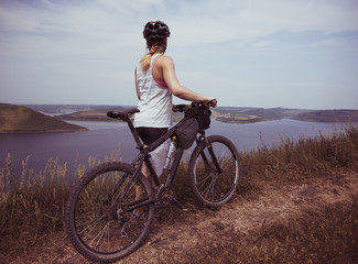 Young bicyclist relax in beautiful nature near river
