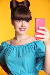 Happy smiling funny teen girl Taking Selfie Photo on Smart Phone