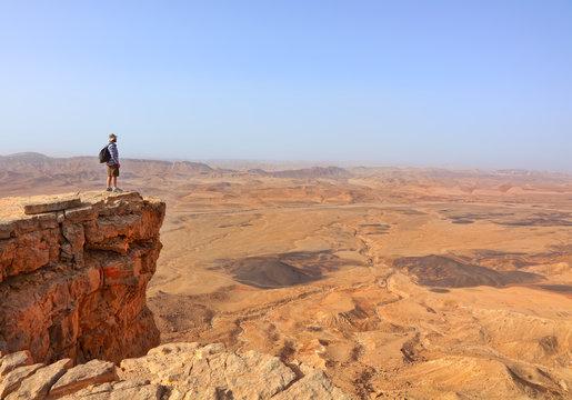 Magic desert landscape / View of Negev stone desert.Traveler on a cliff in the  National geological park HaMakhtesh HaGadol,Large Crater - geological erosion land form, Israel