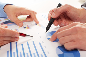 Hands of business people working with graphs.