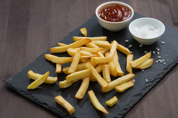 French fries, tomato sauce and salt on a blackboard