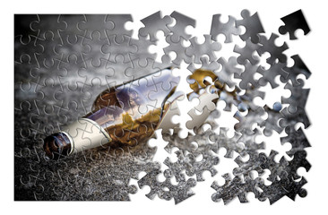 Puzzle of a broken bottle of beer resting on the ground - Alcoholism concept