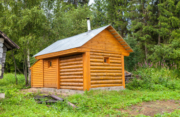 Traditional russian new wooden bath at the bank of lake in summe