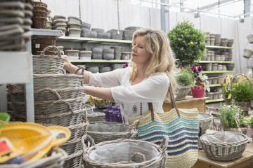 Mature woman choosing baskets in a garden centre, Augsburg, Bavaria, Germany,