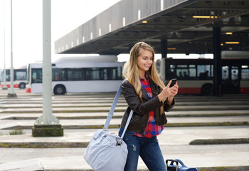Young female traveler looking at mobile phone