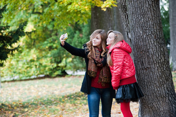 Girls with mobile phone taking pictures in the autumn park