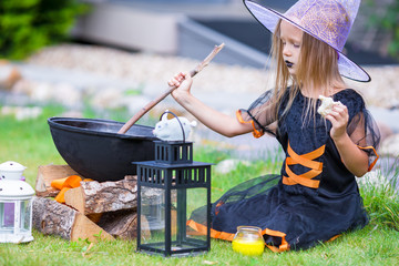 Wall Mural - Little girl wearing witch costume on Halloween outdoors. Trick