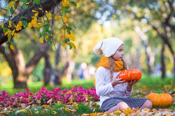 Wall Mural - Adorable little girl with pumpkin outdoors at hallowwen outdoor