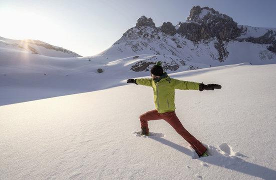 Man doing yoga on snowcapped mountain during sunrise, Tyrol, Austria