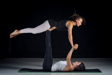 two girls performing acro-yoga poses