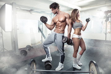 beautiful young sporty sexy couple workout in gym