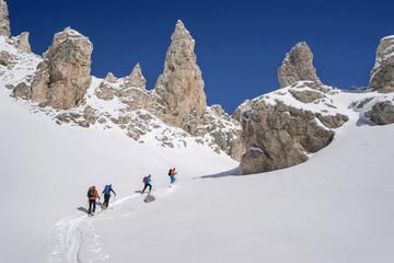 Ski mountaineers climbing on snowy peak, Val Gardena, Trentino-Alto Adige, Italy