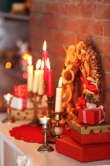 Christmas decorations and candles on mantelpiece